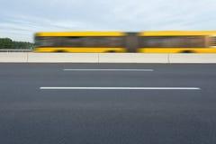 在黄色城市公共汽车的侧视图在行动迷离 免版税库存图片