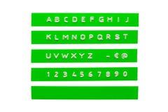 在绿色塑料磁带上的压印的字母表 库存照片
