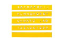 在黄色塑料磁带上的压印的字母表 免版税库存图片