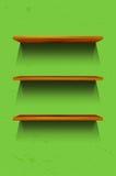 在绿色墙壁上的三个空的木架子 库存照片