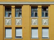 在黄色墙壁上的八个窗口 免版税库存照片