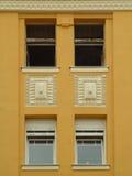 在黄色墙壁上的四个窗口 库存照片
