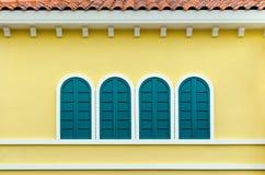 在黄色墙壁上的四个绿色被成拱形的窗口 库存照片