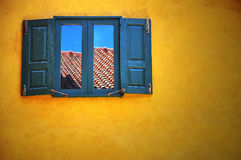 在黄色墙壁上的木窗口 库存图片