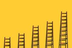 在黄色墙壁上的梯子 库存照片