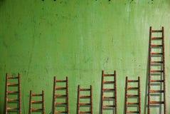 在绿色墙壁上的梯子 库存图片