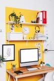 在黄色墙壁上的现代创造性的工作区 库存照片