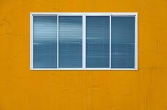 在黄色墙壁上的现代玻璃窗 库存图片
