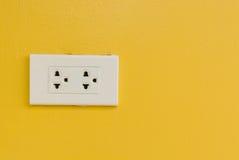 在黄色墙壁上的白色电火花塞 免版税库存图片