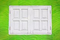 在绿色墙壁上的白色窗口。 库存照片