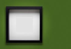 在绿色墙壁上的空白的厚实的照片框架 免版税库存图片