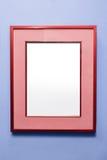 在紫色墙壁上的空白的红色框架 库存照片