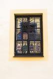 在黄色墙壁上的窗口有装饰金属元素的 库存图片