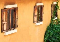 在黄色墙壁上的老木窗口 库存图片