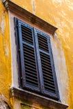 在黄色墙壁上的老木蓝色窗口 库存图片