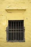 在黄色墙壁上的老窗口 库存照片