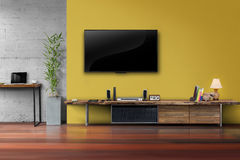 在黄色墙壁上的被带领的电视有木桌媒介家具的 免版税库存照片