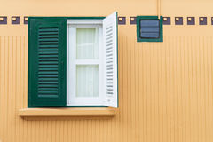 在黄色墙壁上的绿色窗口 免版税库存图片