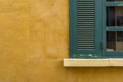 在黄色墙壁上的绿色玻璃窗口 库存图片