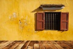 在黄色墙壁和木头地板上的打开窗口 免版税库存图片