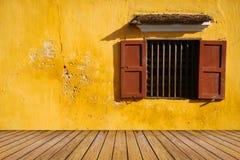 在黄色墙壁和木头地板上的打开窗口 免版税库存照片