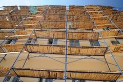 在黄色墙壁附近的木脚手架 免版税库存图片