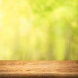 在绿色夏天森林背景的木桌 免版税库存照片