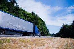在绿色夏天路的半蓝色卡车现代alumnum拖车 免版税图库摄影