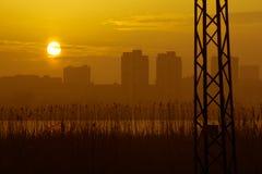 在黄色多云日落的电源杆剪影 库存图片