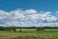 在绿色多小山谷上的多云天空 库存图片