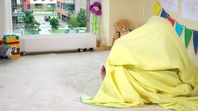 在黄色套下的淘气儿童女孩皮在地板上在家 股票录像