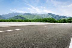 在绿色山前面的柏油路 免版税库存图片