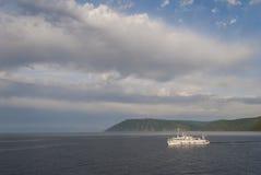 在绿色山背景的一艘船 免版税库存照片