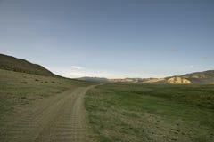 在绿色山谷中的土路 图库摄影