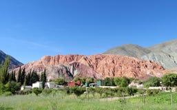 在绿色山谷和村庄上的红色山 免版税图库摄影