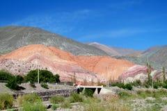 在绿色山谷和村庄上的红色山 免版税库存照片