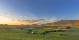 在绿色山谷的金黄日出 库存照片