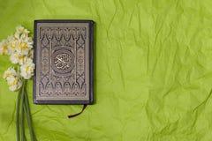 在绿色工艺的圣洁古兰经和黄水仙花束裱糊背景 图库摄影