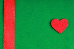 在绿色布料背景的红色木装饰心脏。 免版税库存照片