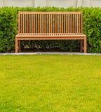 在绿色布什的长木凳 库存图片