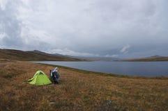 在绿色帐篷附近的Enduro摩托车单独旅客在湖黑暗的幽暗雾干草原岸  免版税库存图片