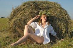 在黄色干草的美好的白肤金发的国家女孩sittitng与花 免版税库存图片