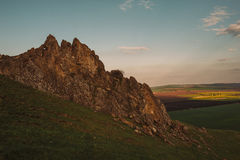 在绿色平原的大峭壁在日落 免版税库存图片