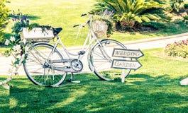 在绿色庭院的老白色婚礼自行车在花附近 免版税库存图片