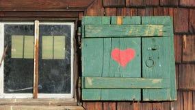 在绿色快门的红色心脏 免版税库存图片