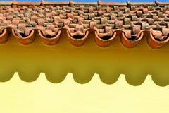 在黄色房子墙壁上的陶瓷砖和树荫 库存图片