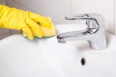 在黄色手套的手与海绵清洁水槽 库存照片