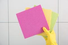 在黄色手套的手拿着多彩多姿的清洁布 图库摄影