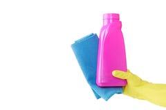 在黄色手套的手拿着桃红色瓶液体洗涤剂和duston白色背景的蓝色旧布 清洁 库存图片