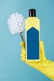 在黄色手套的手拿着瓶洗手间的在蓝色背景的液体洗涤剂和刷子 库存图片